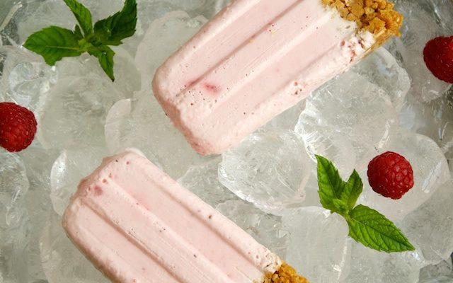 Polos, helados, paletas o popsicles de tarta de queso con fresas y frambuesa.